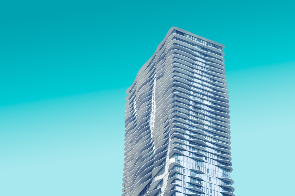 gray high rise building with teal background