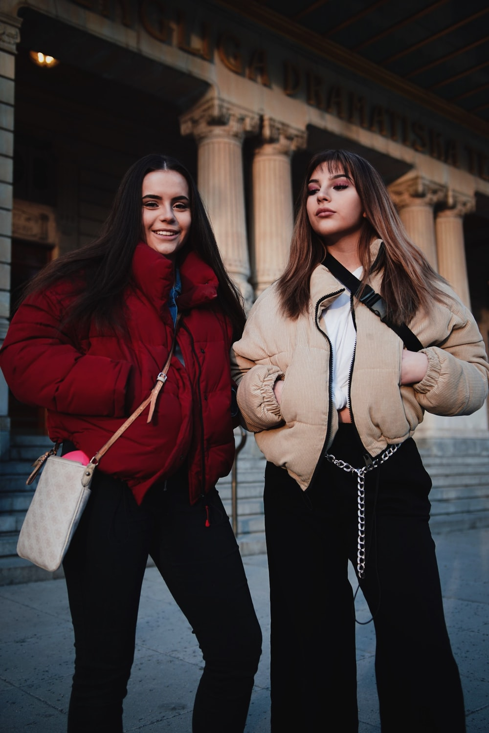 two woman standing near building