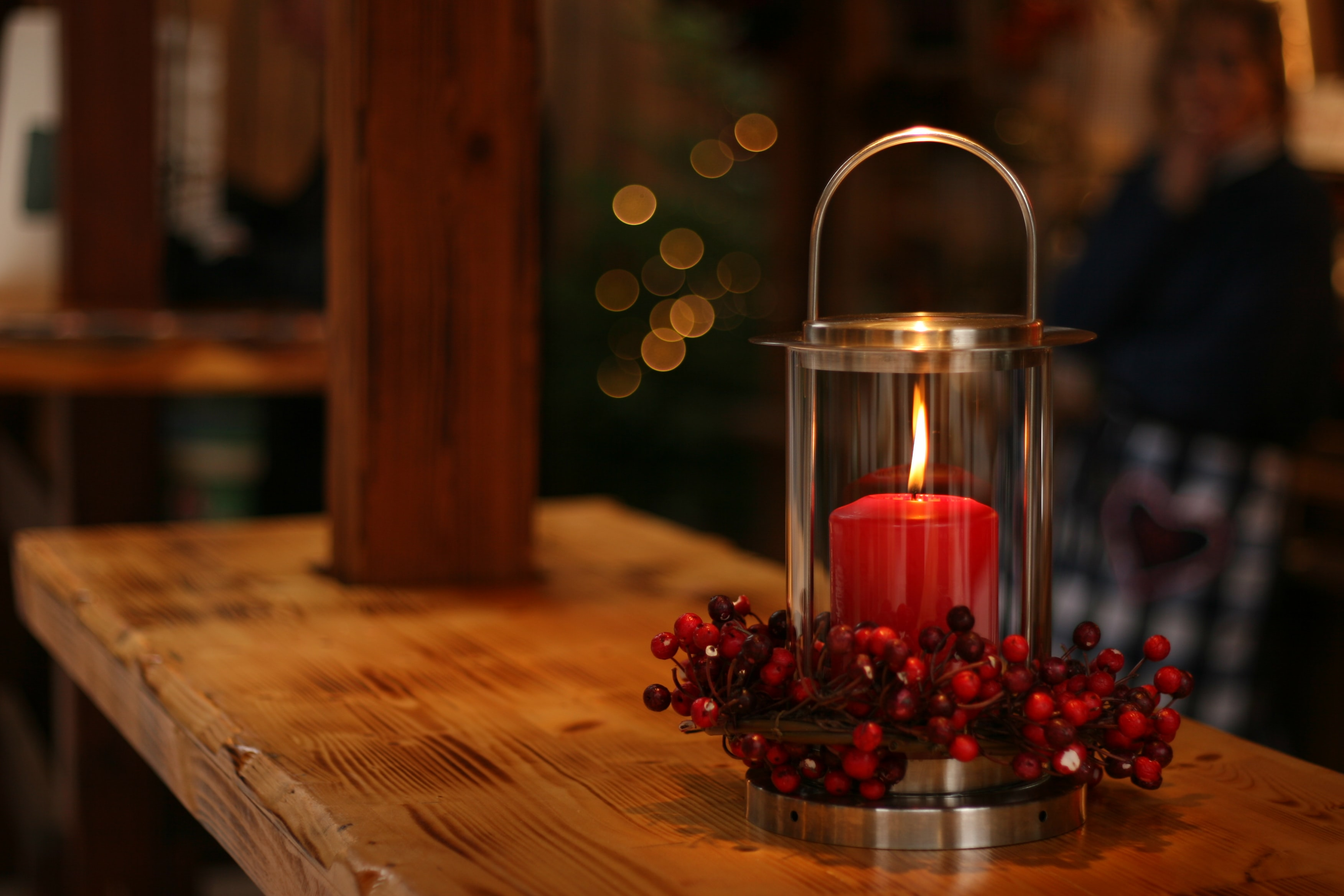 red lighted candle on brown wooden frame