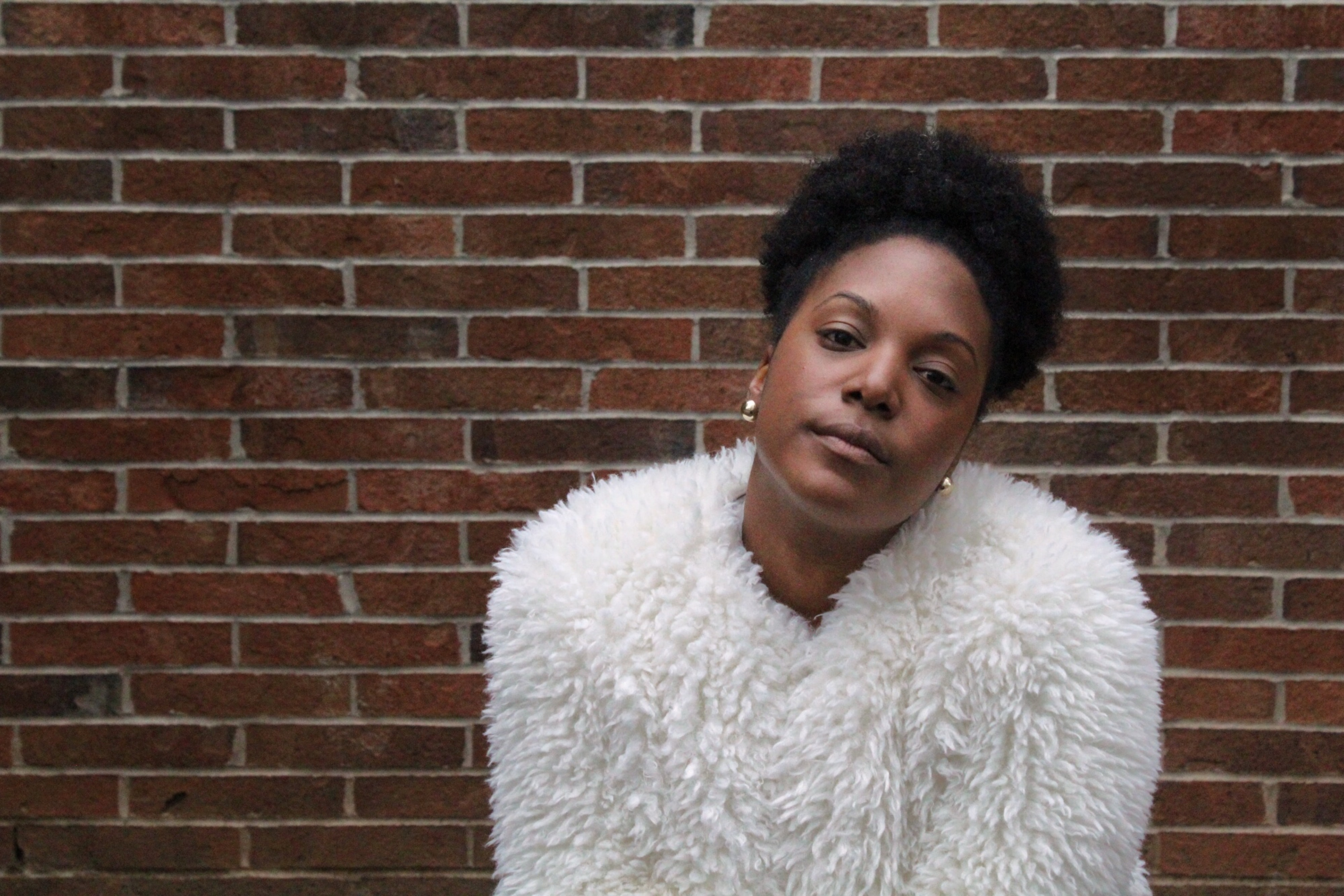 woman in white fur coat in front of the brick wall