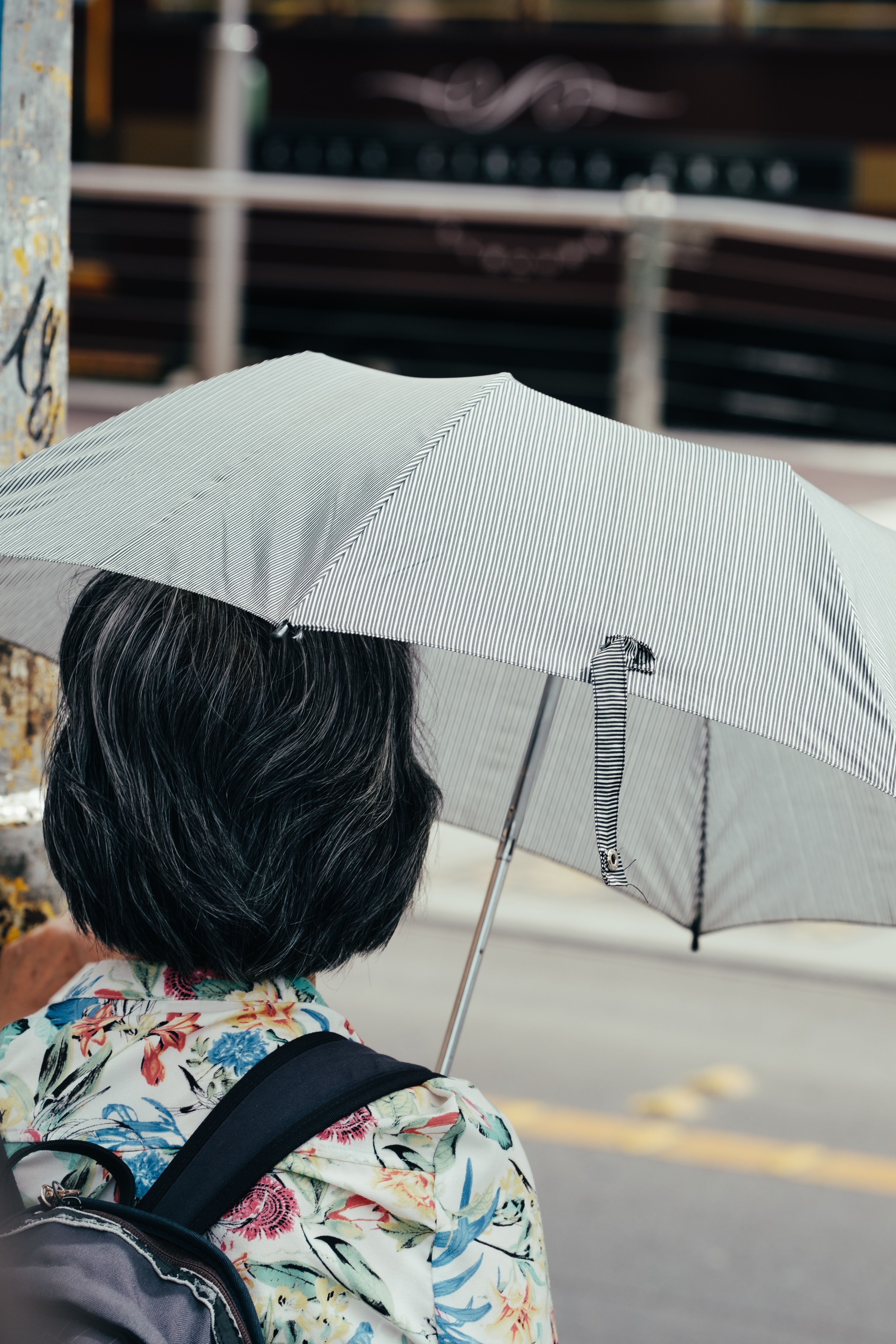 woman under grey umbrella near road