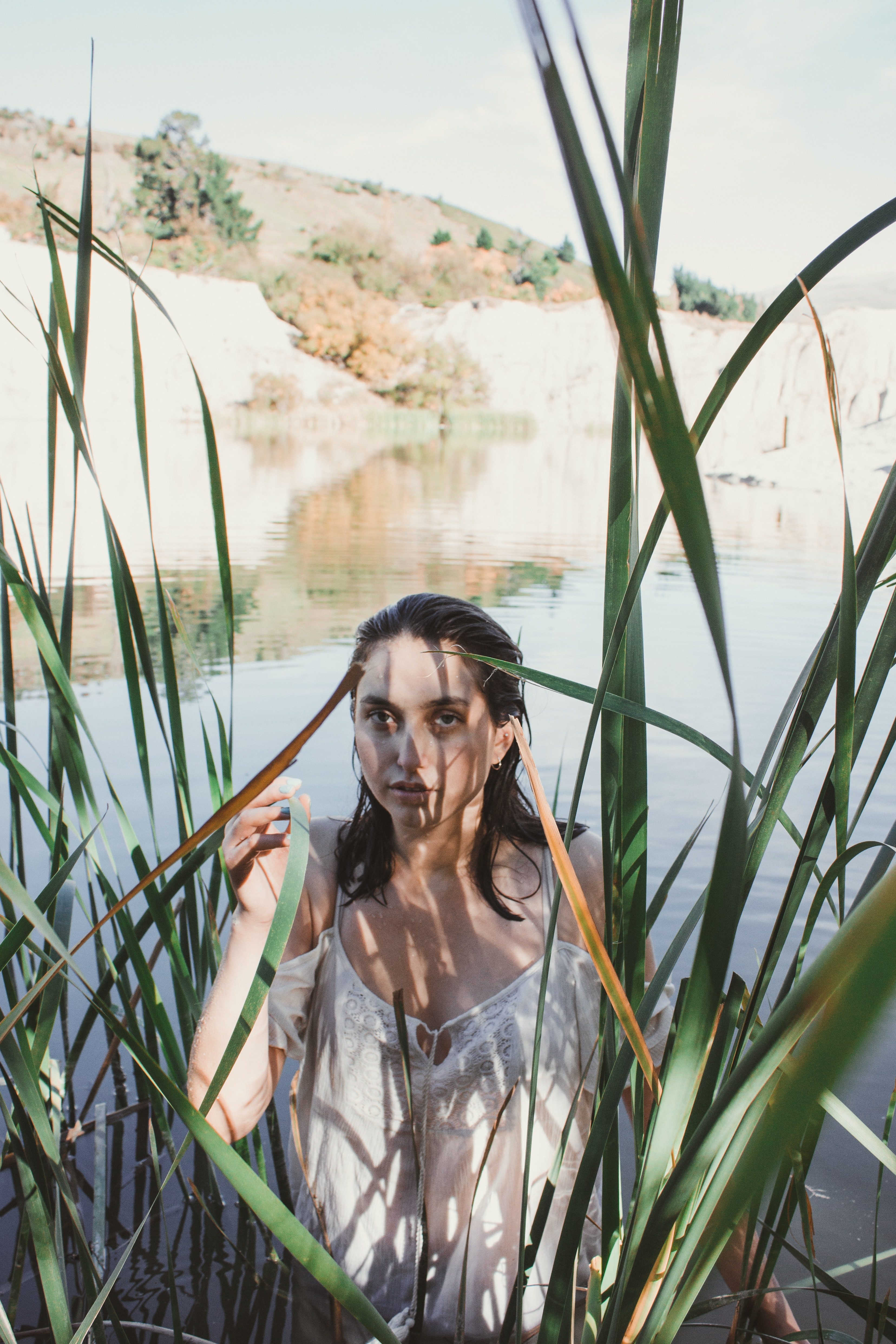 woman standing on lake surrounded by green leaf plants