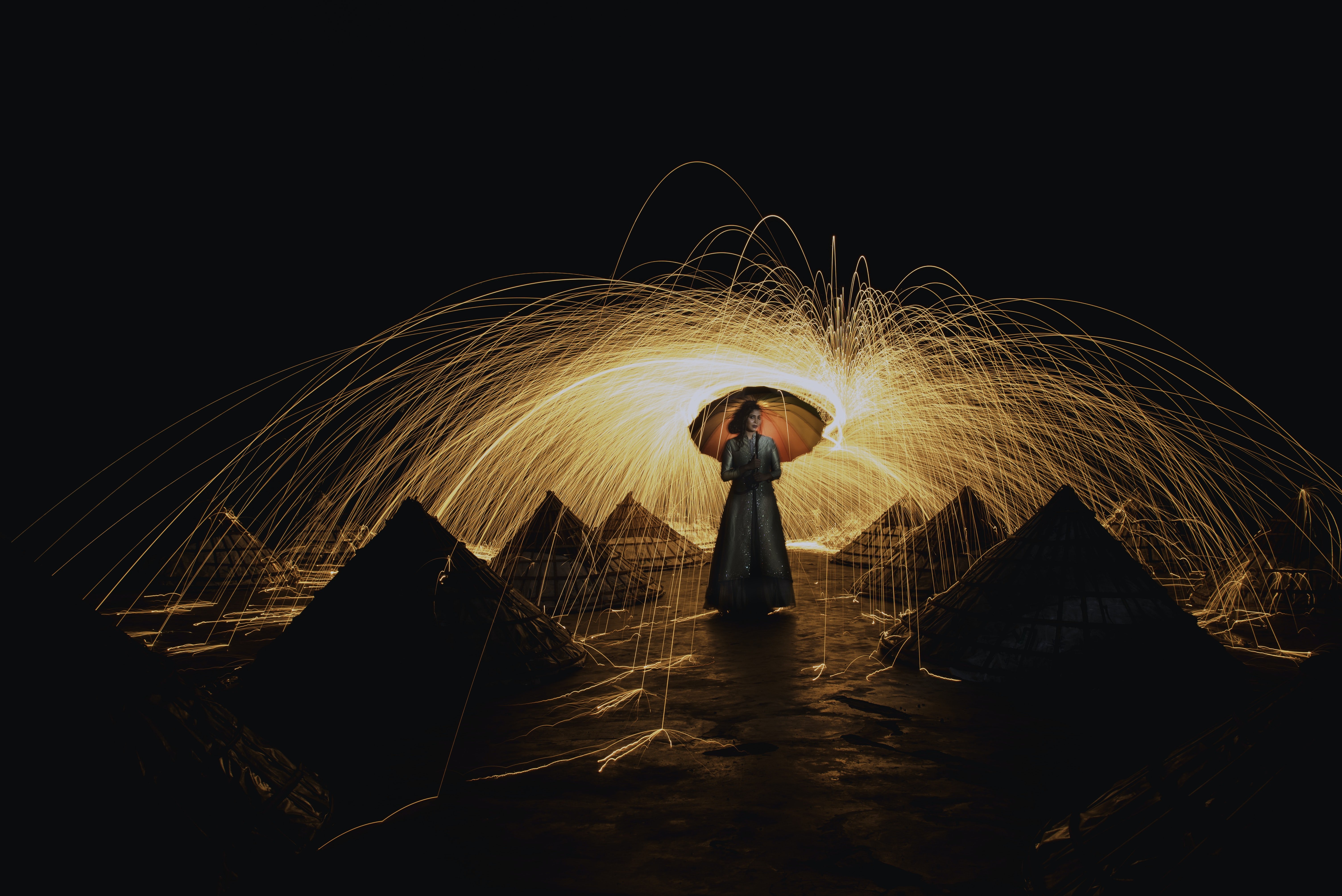 time lapse photography of woman standing in between pyramids holding umbrella