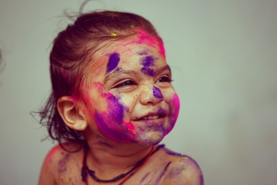 selective focus photography toddler girl with face paint holi zoom background
