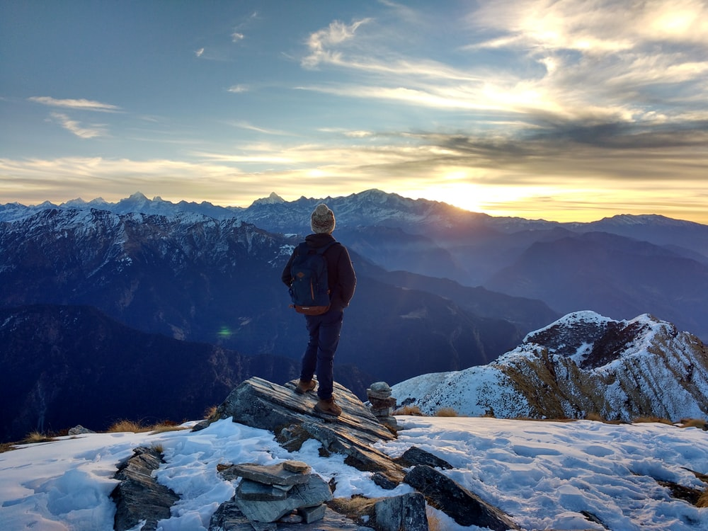 person standing on top of the mountain facing sunrise