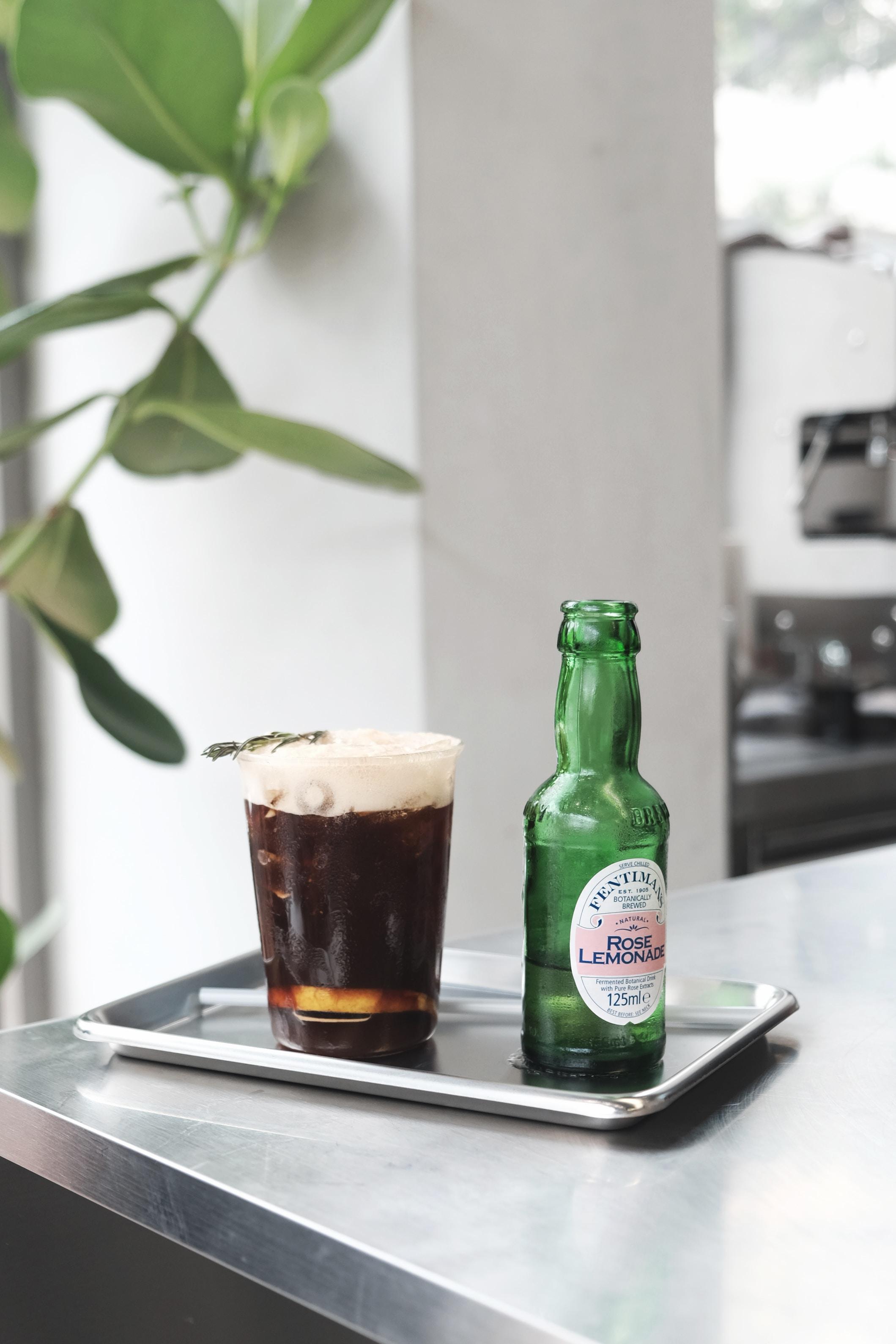 green glass bottle beside drinking glass
