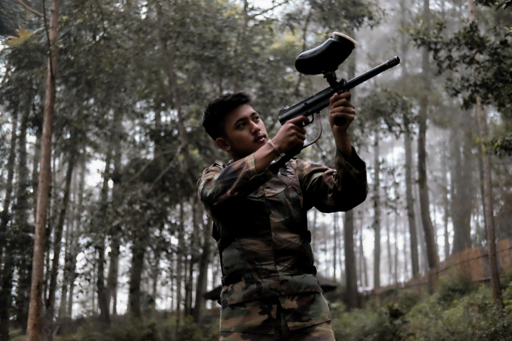 soldier holding paintball gun on forest