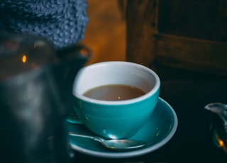 teal and white ceramic cup half-filled with coffee
