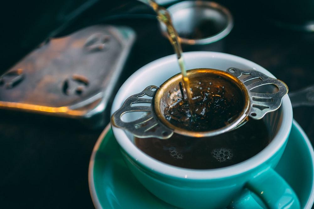 closeup photo of green ceramic cup with tea