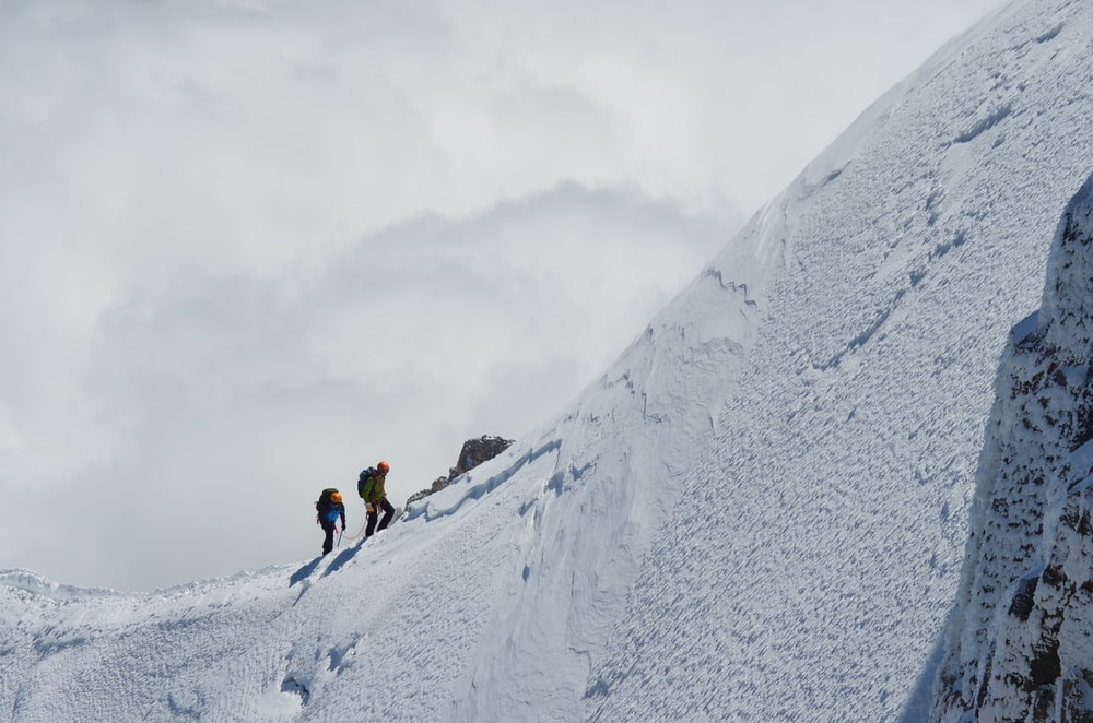 two persons trekking on snow mountain