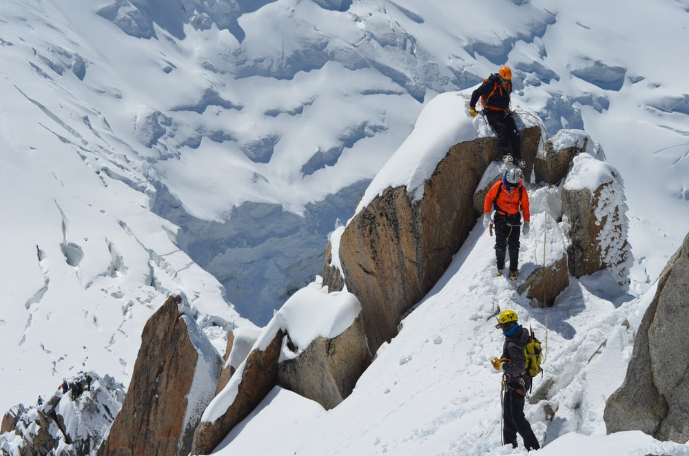 three person trekking on snow field mountain at daytime