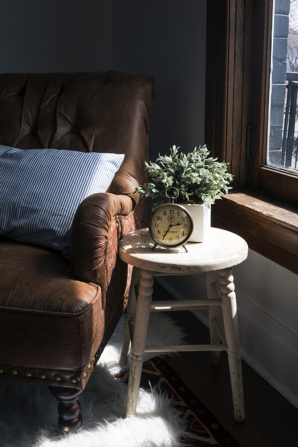 brown leather padded sofa armchair next to white wooden stool chair with round gray metal analog clock