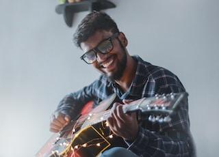 smiling man sitting while playing guitar