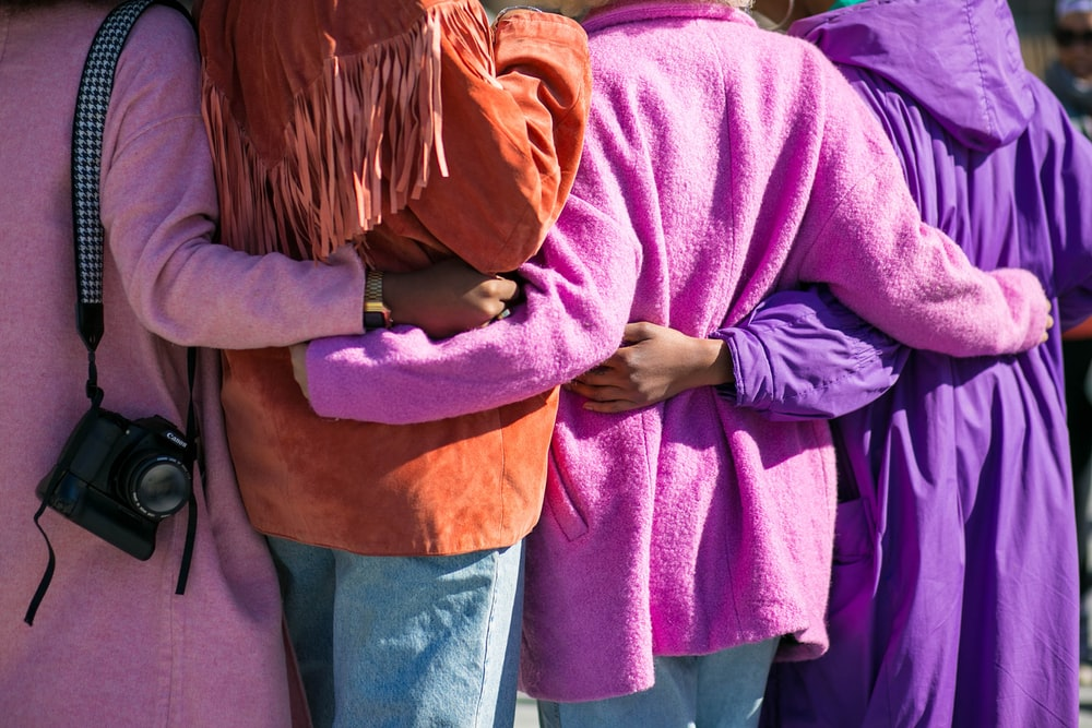 four person holding each others waist at daytime