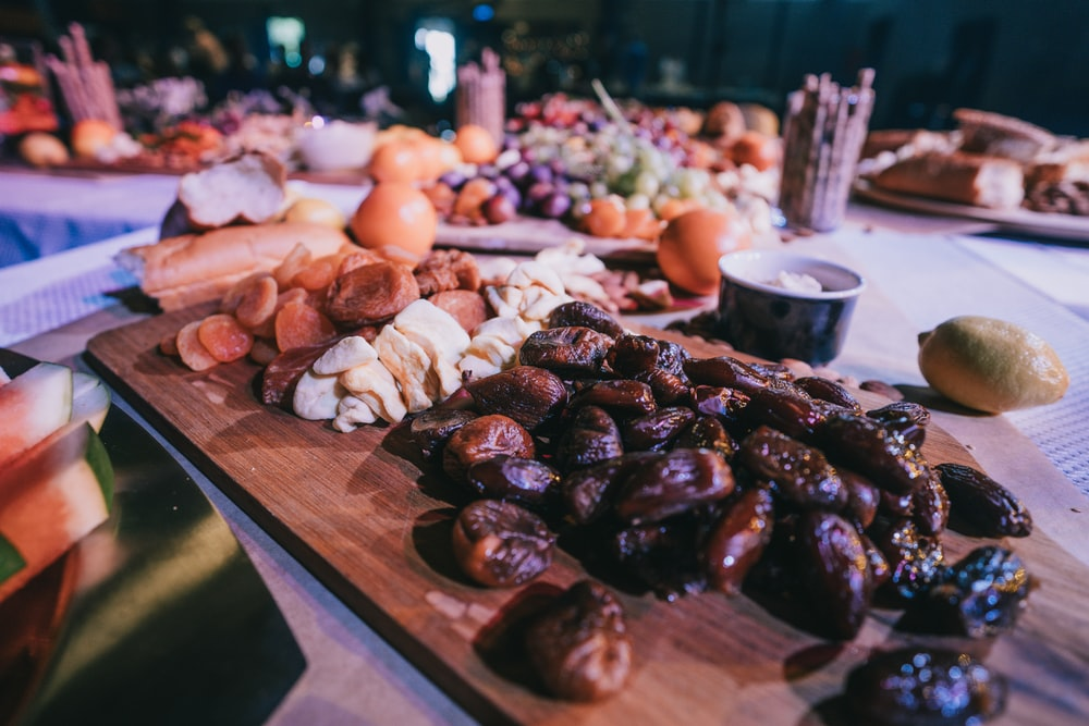 closeup photo of dates and breads on brown wooden tray