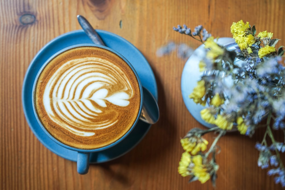 flat lay photography of coffee near flowers