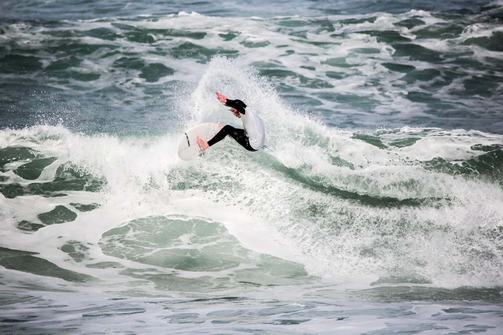 person surfing on beach during daytime photo