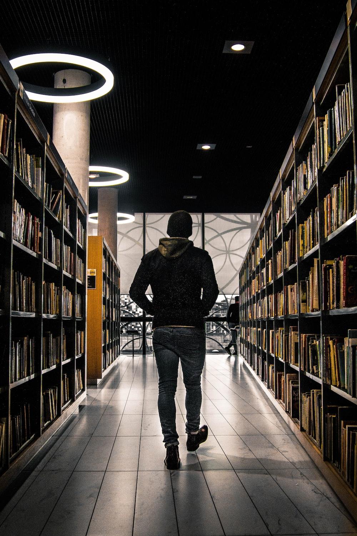 man walking between bookshelf