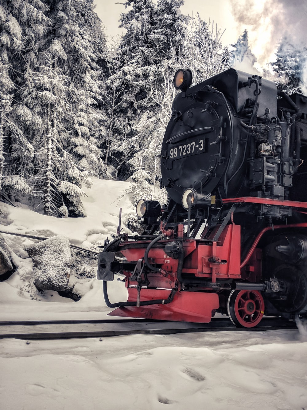black and red steam train on railway during daytime