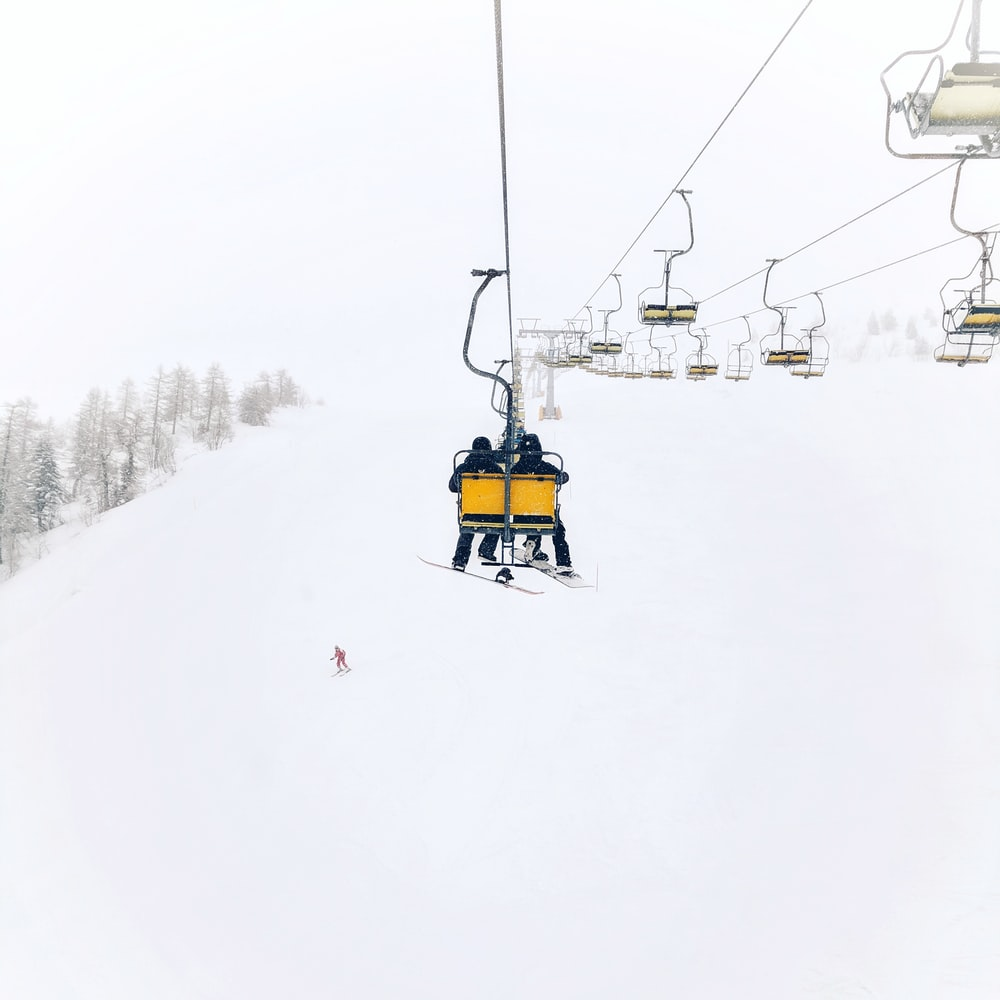 two person riding on cable transportation through top of the hill during winter