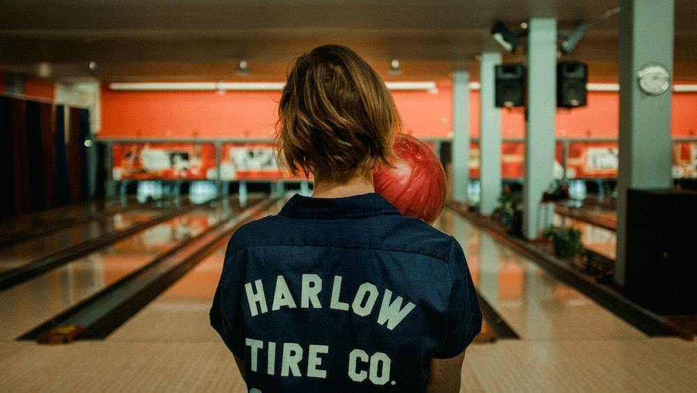 person holding bowling ball facing bowling pins