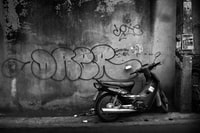 motorcycle park near wall grayscale photography