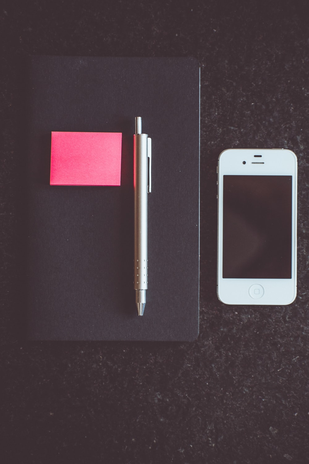 white iPhone 5 beside pen and book
