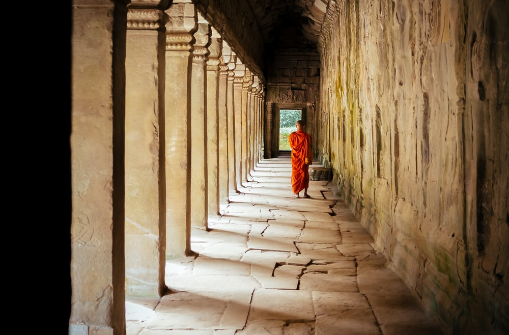 selective focus photography of monk at corridor