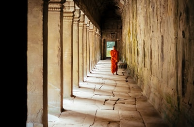 selective focus photography of monk at corridor cambodia zoom background