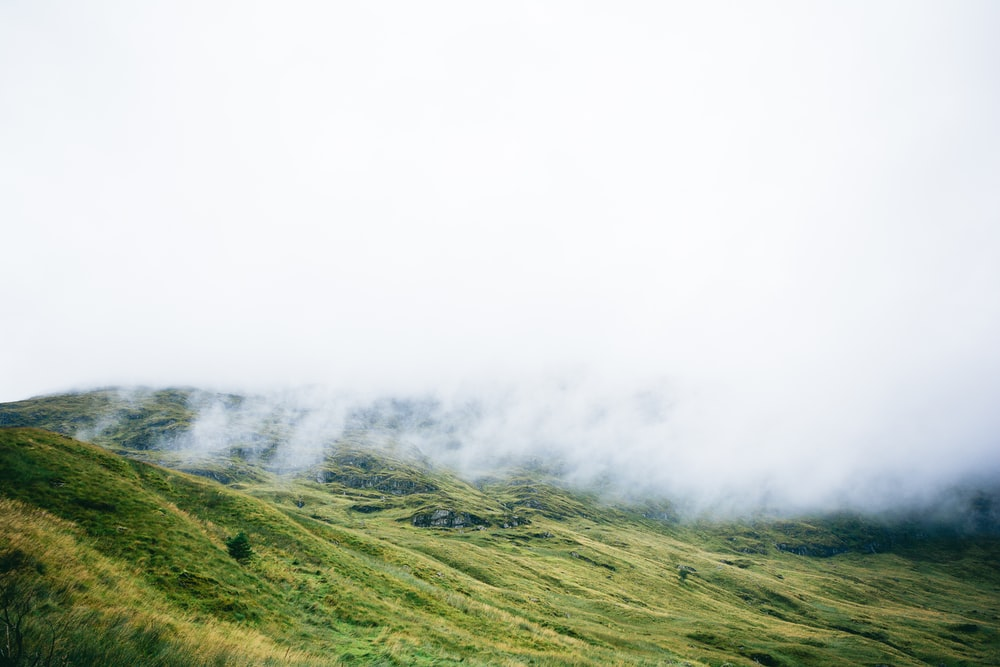 time lapse photography of hill and clouds