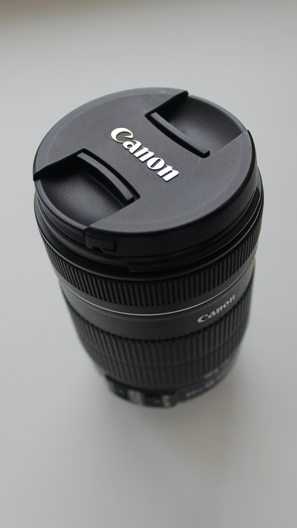 black Canon DSLR camera lens on white tabletop