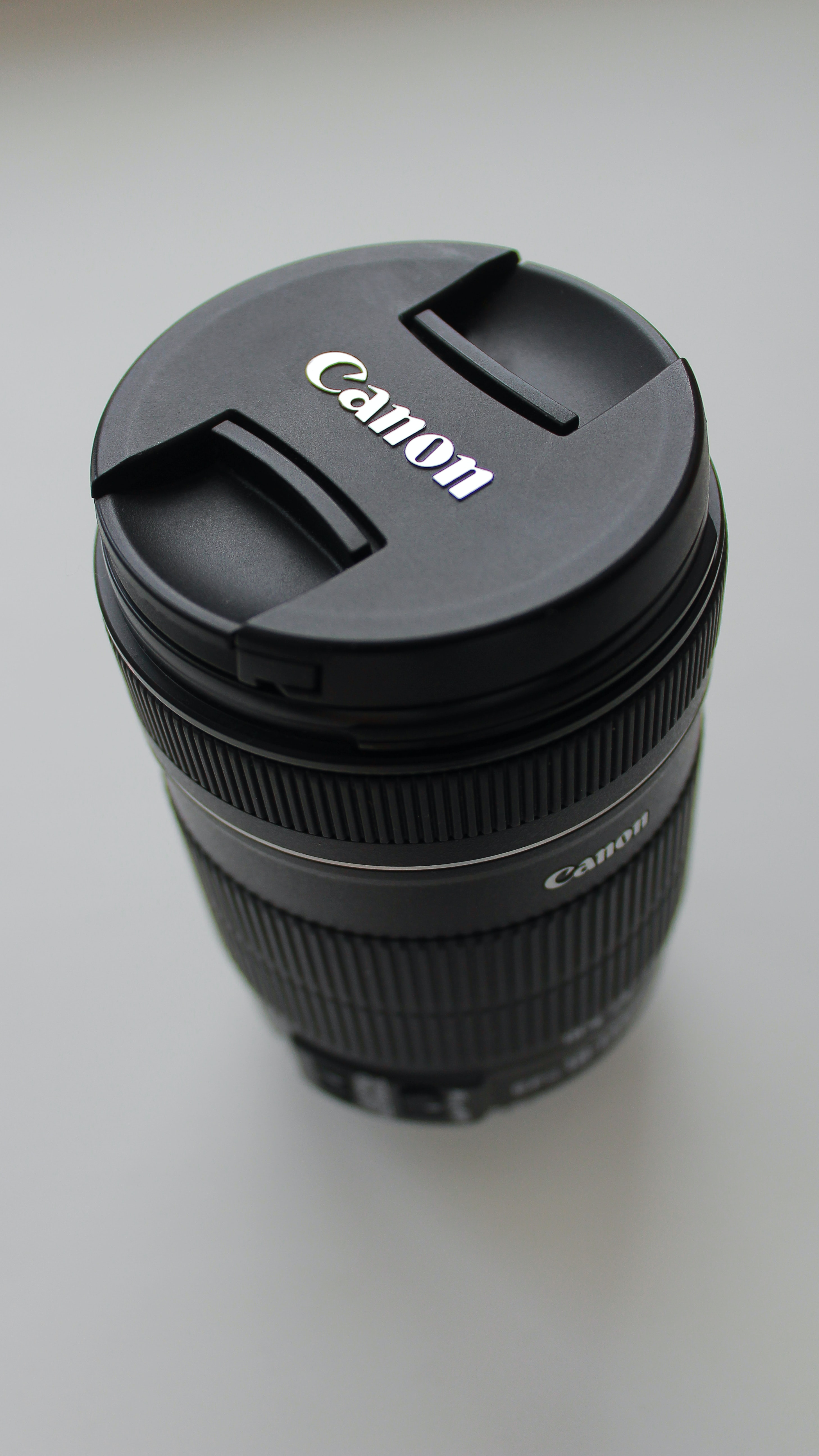 black Canon DSLR camera lens on white tabletop