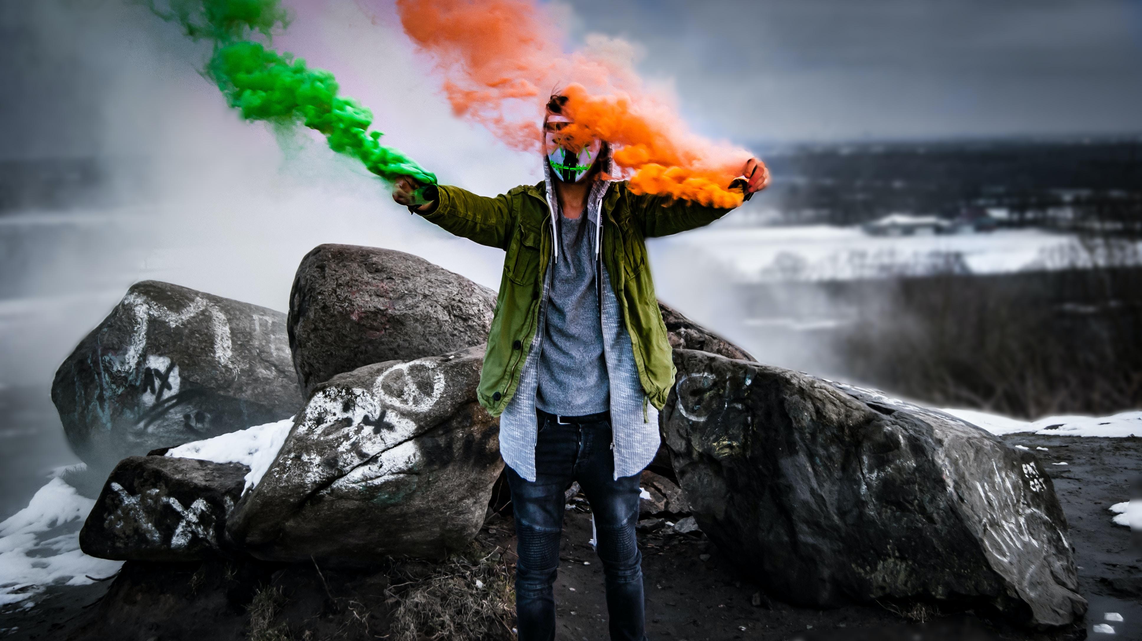 man holding smoke flares