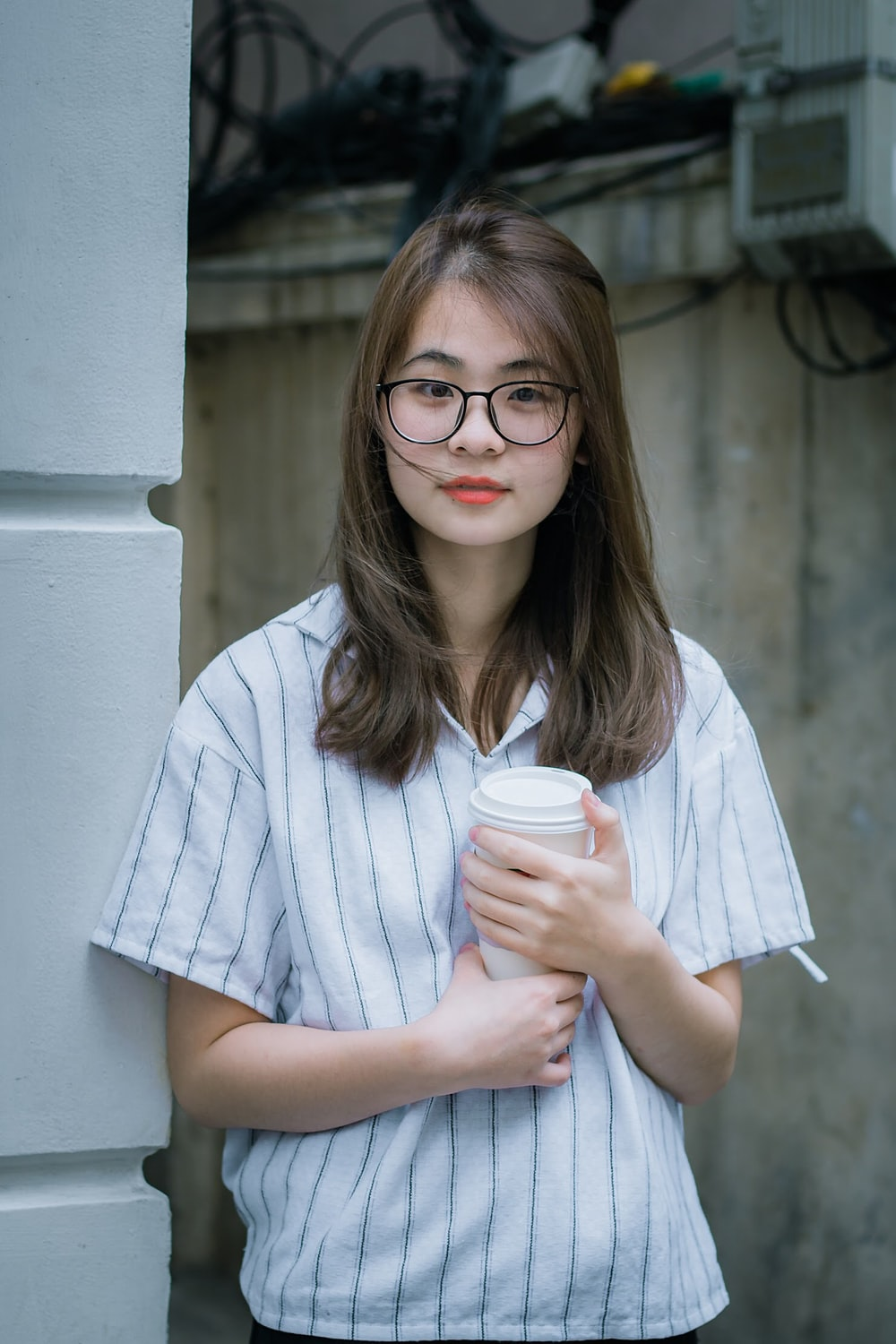 woman holding cup beside wall