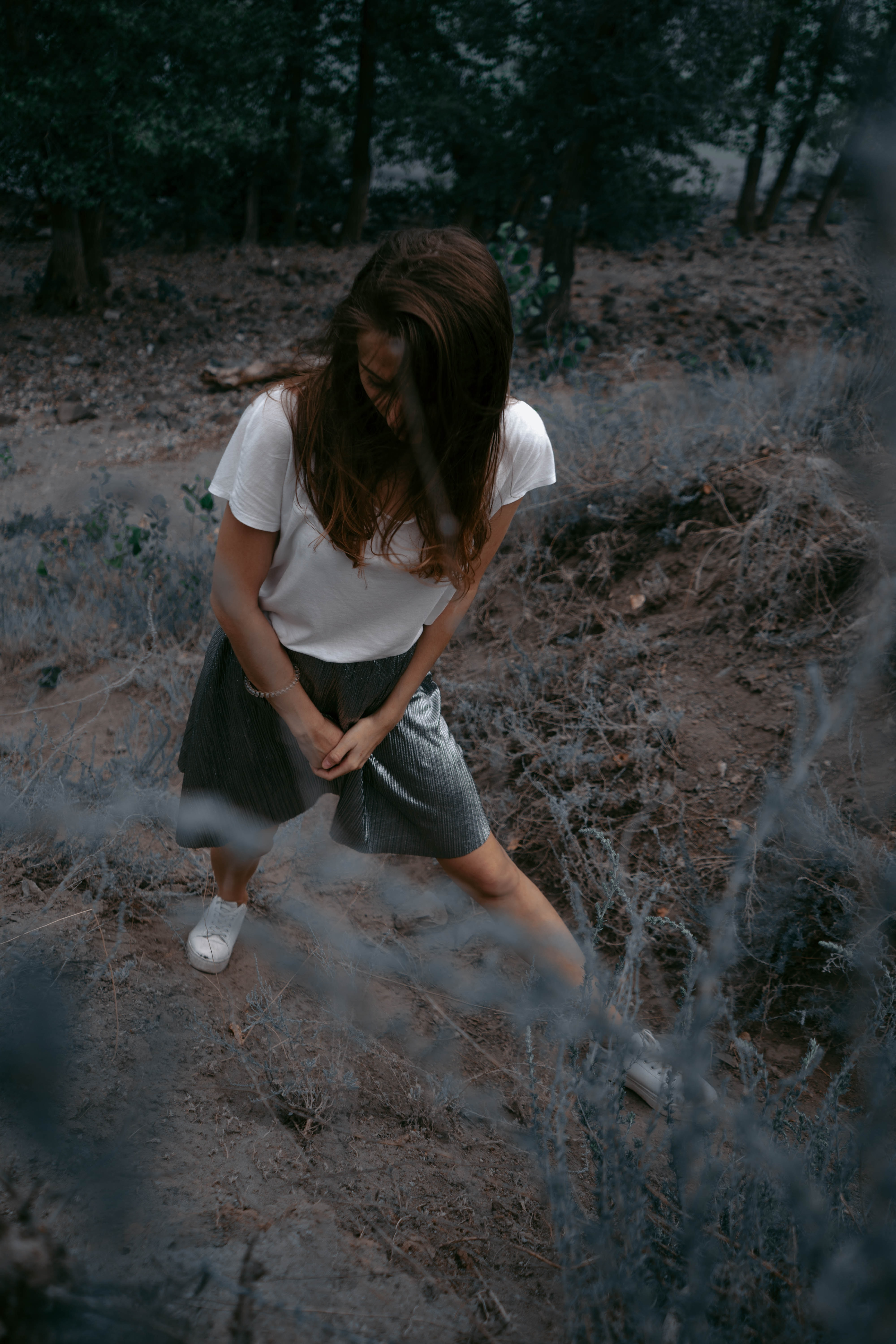 woman standing on ground surround by trees