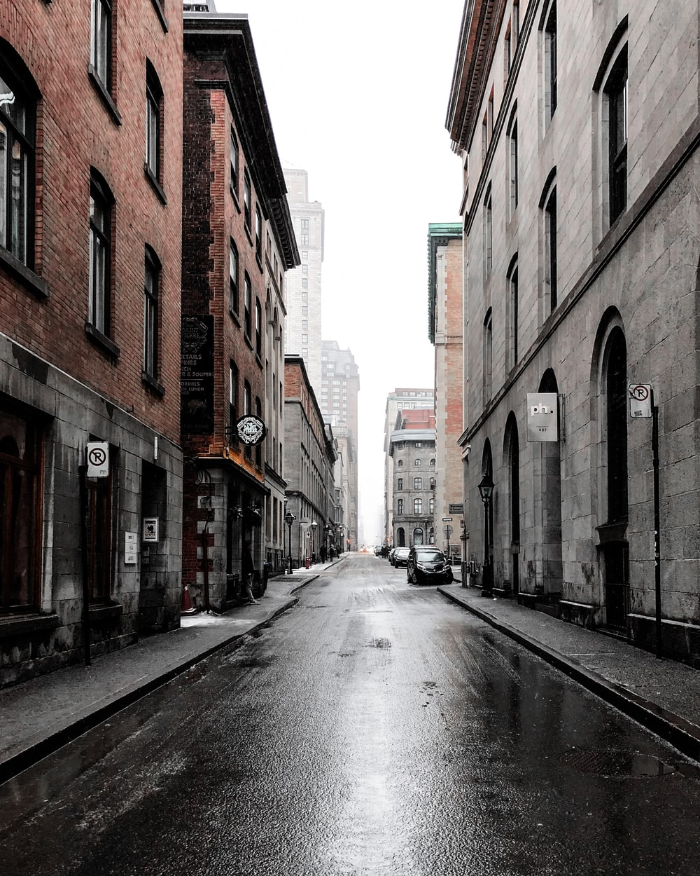 person standing beside car between buildings