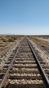 train track under blue sky