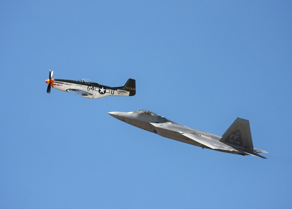 white-and-black monoplane and gray jet