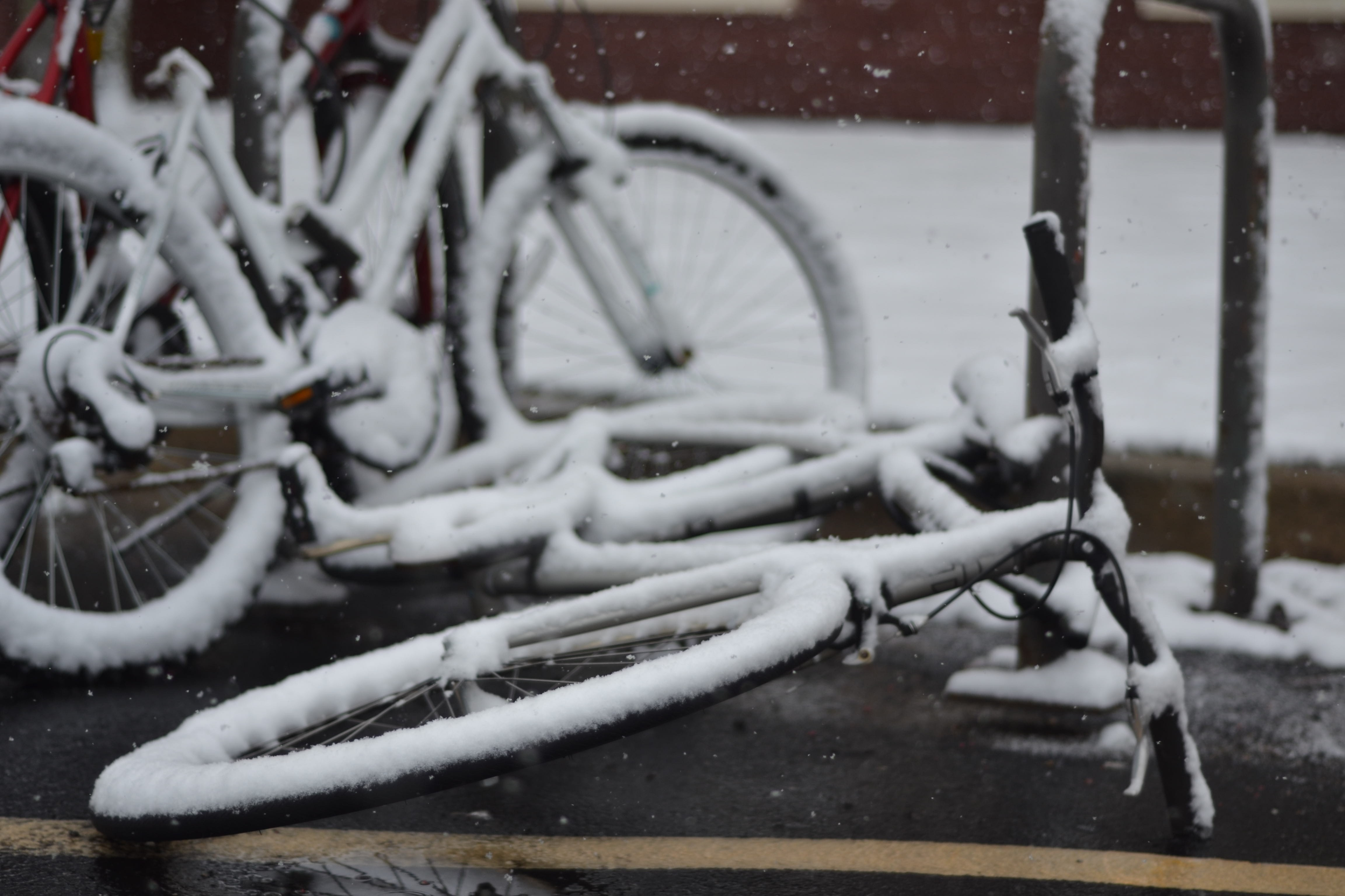 two snow covered bicycle on street
