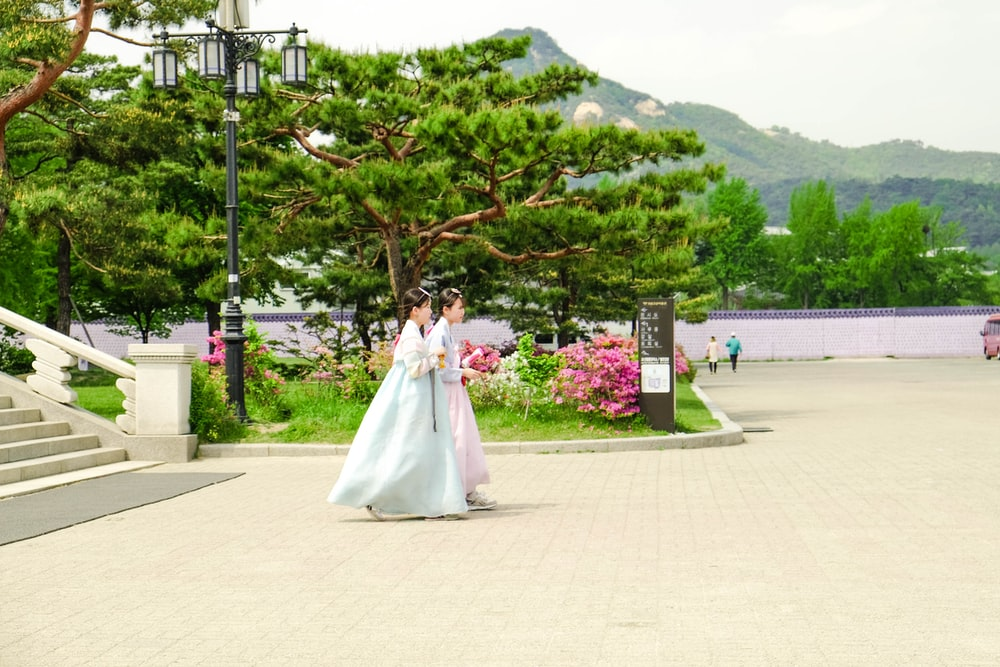 woman in white wedding dress standing near green tree during daytime