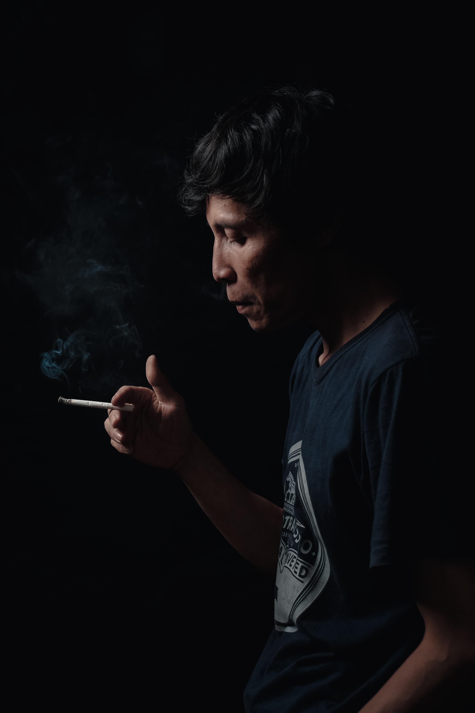 man holding cigarette stick