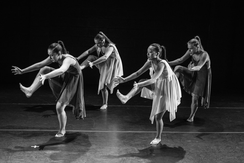 four women dancing grayscale photography