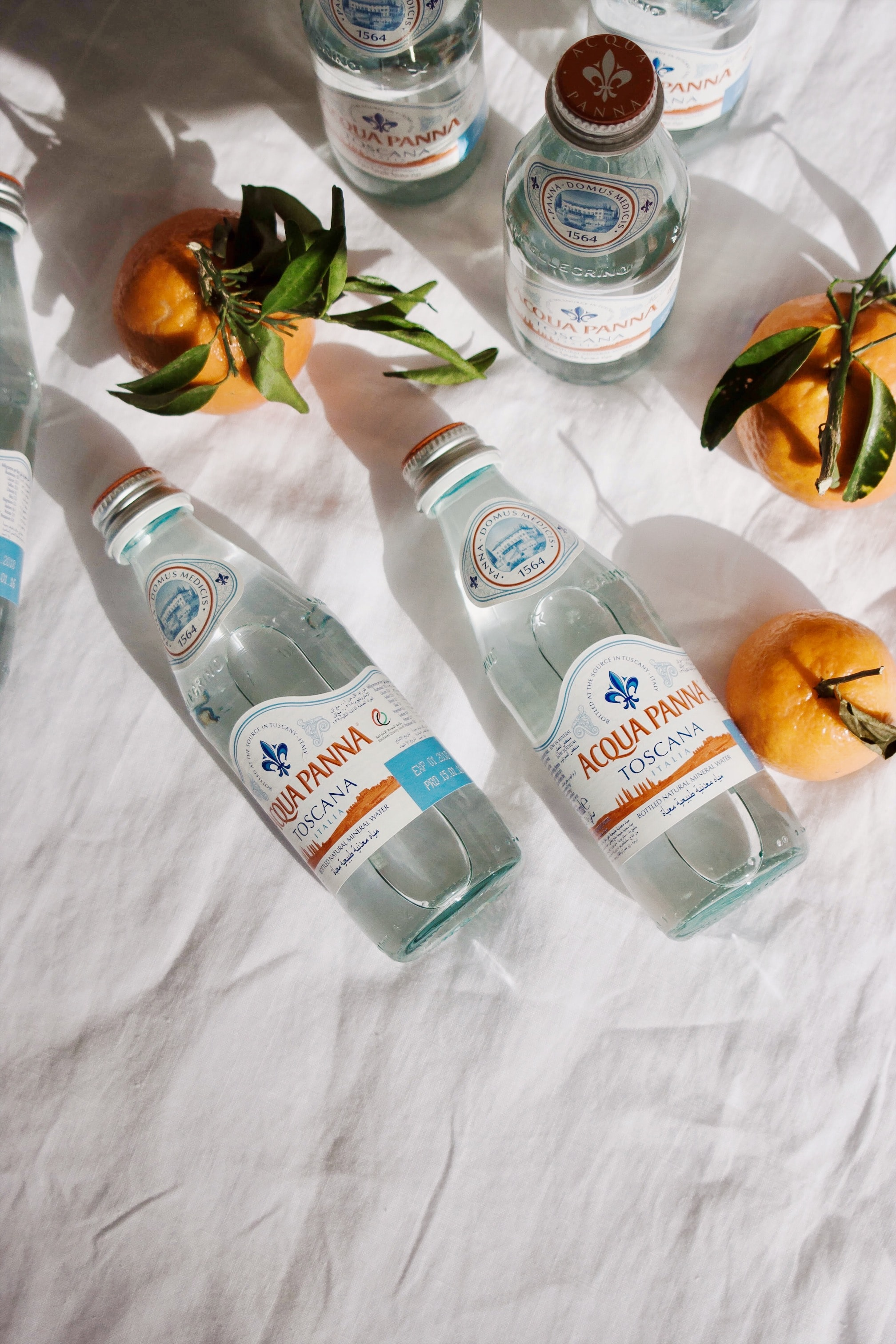 two Acqua Panna bottles beside orange fruits