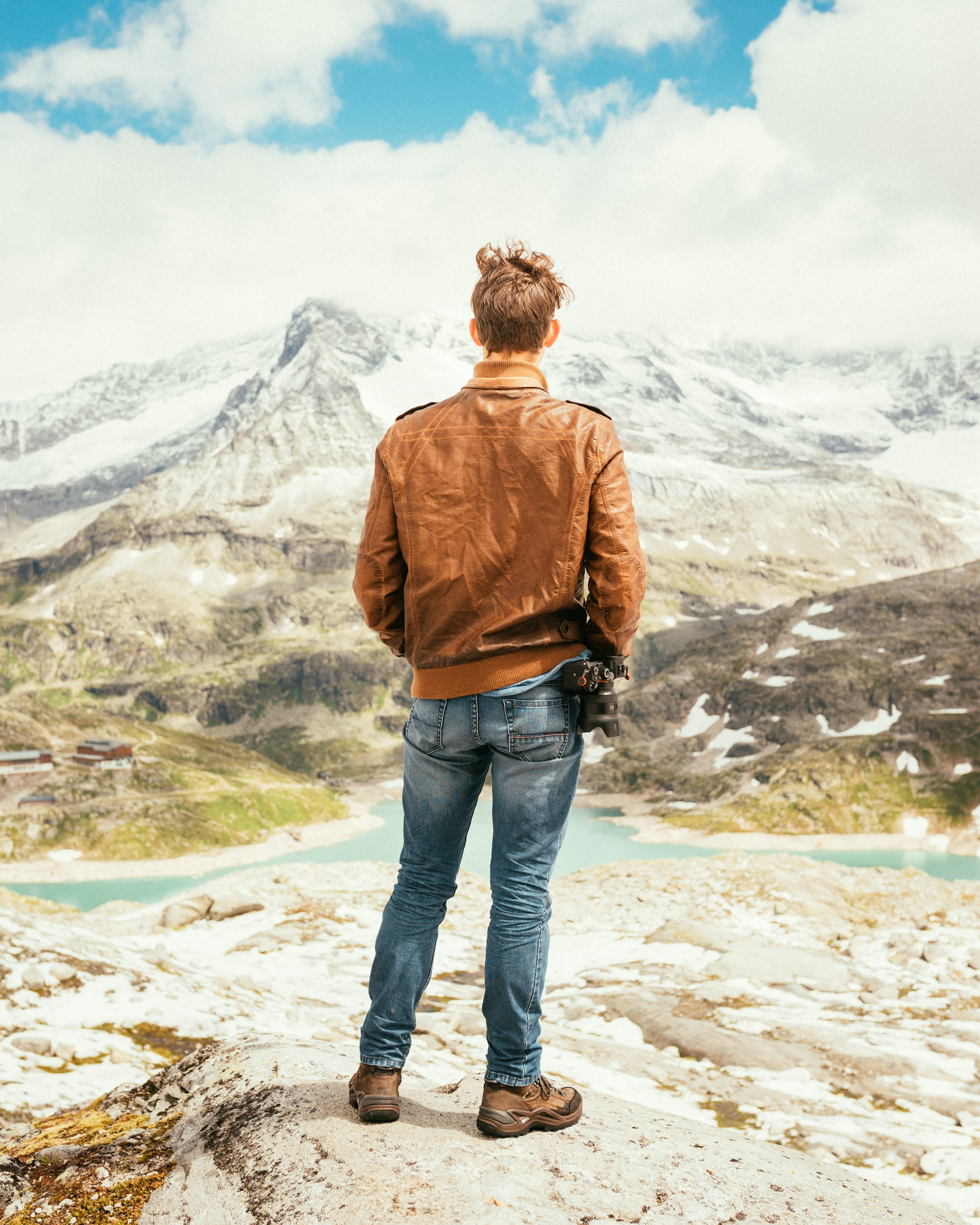 man standing on rock facing lake and mountains during daytime