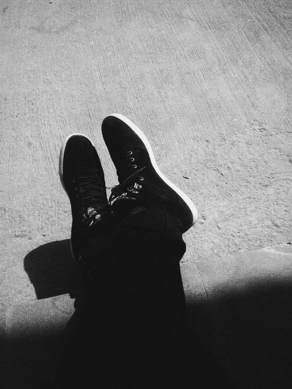 be9d7003c0d grayscale photography of person wearing black sneakers sitting on floor