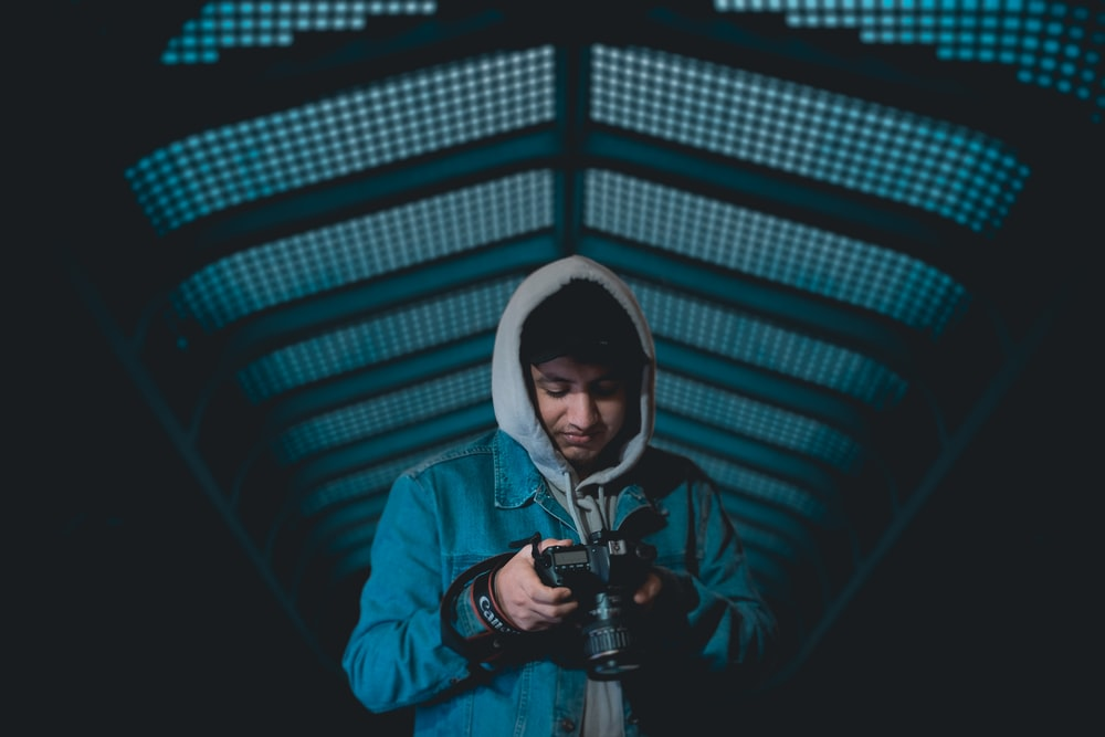 man with blue hoodie holding black Canon DSLR in dark room