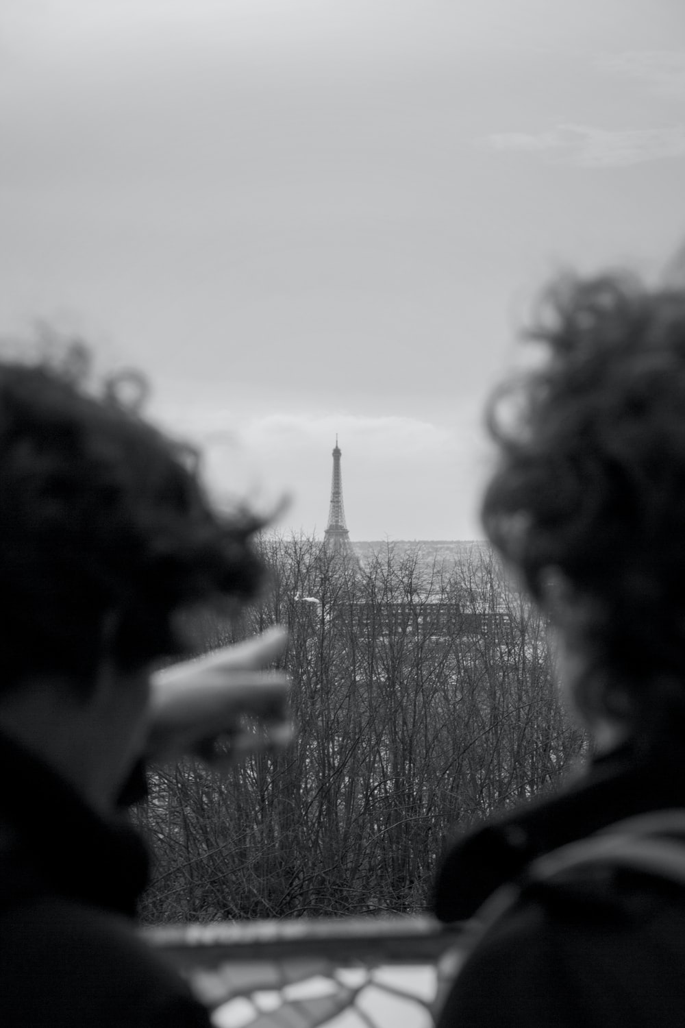 grayscale photo of man pointing at Eiffel tower