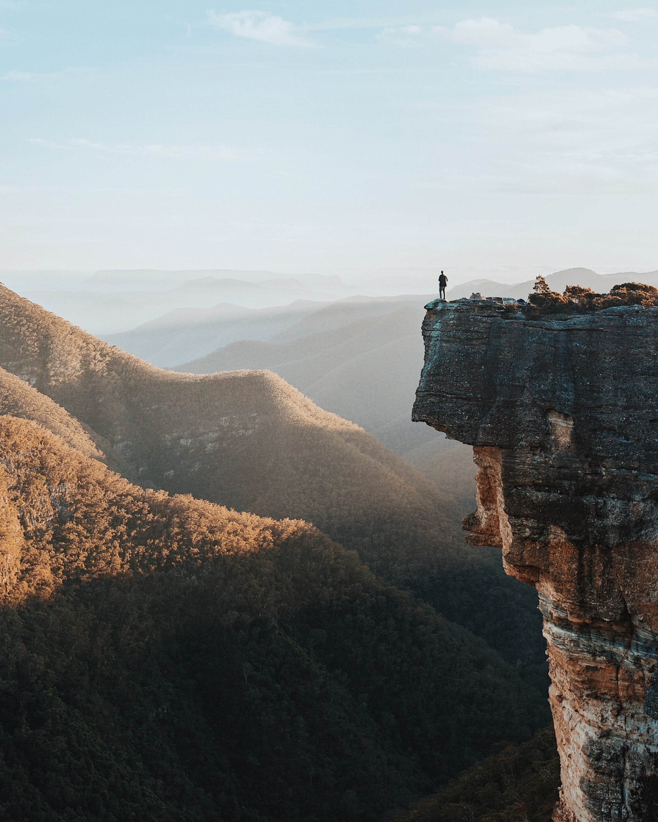 man standing on rock cliff overlooking mountains