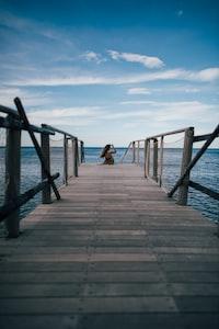 woman sitting on sea dock