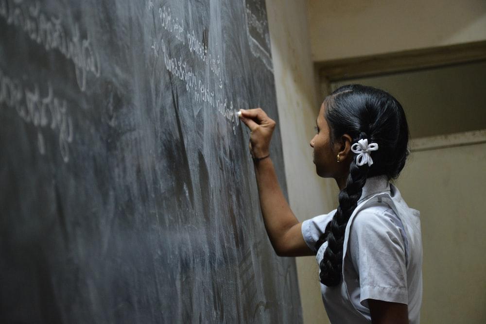 woman standing writing on black chalkboard